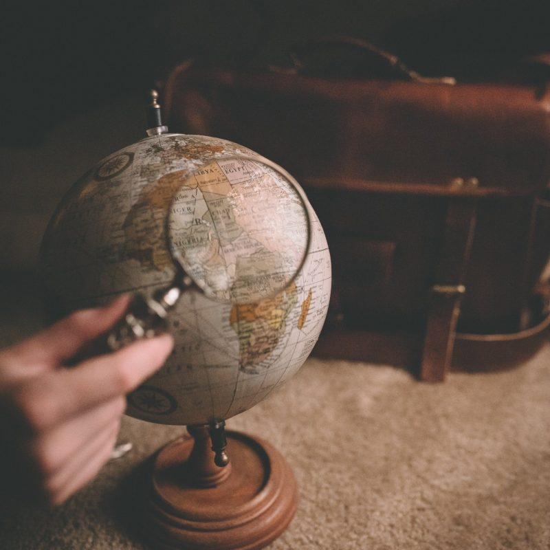 Stop living small - globe with magnifying glass